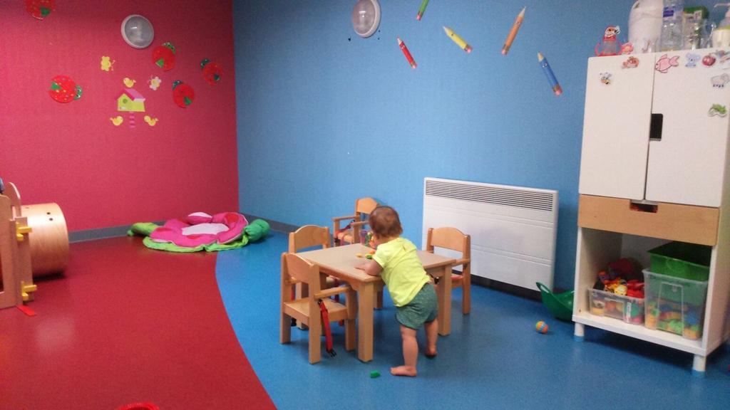 Un enfants qui joue sur une petite table en bois