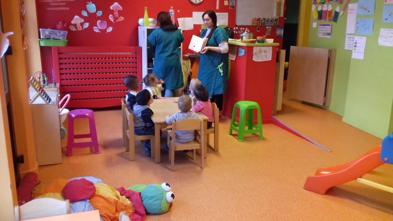 Des enfants assis à une petite table avec un adulte qui montre un livre
