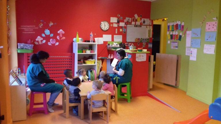 Des enfants assis à une table avec leur éducateurs