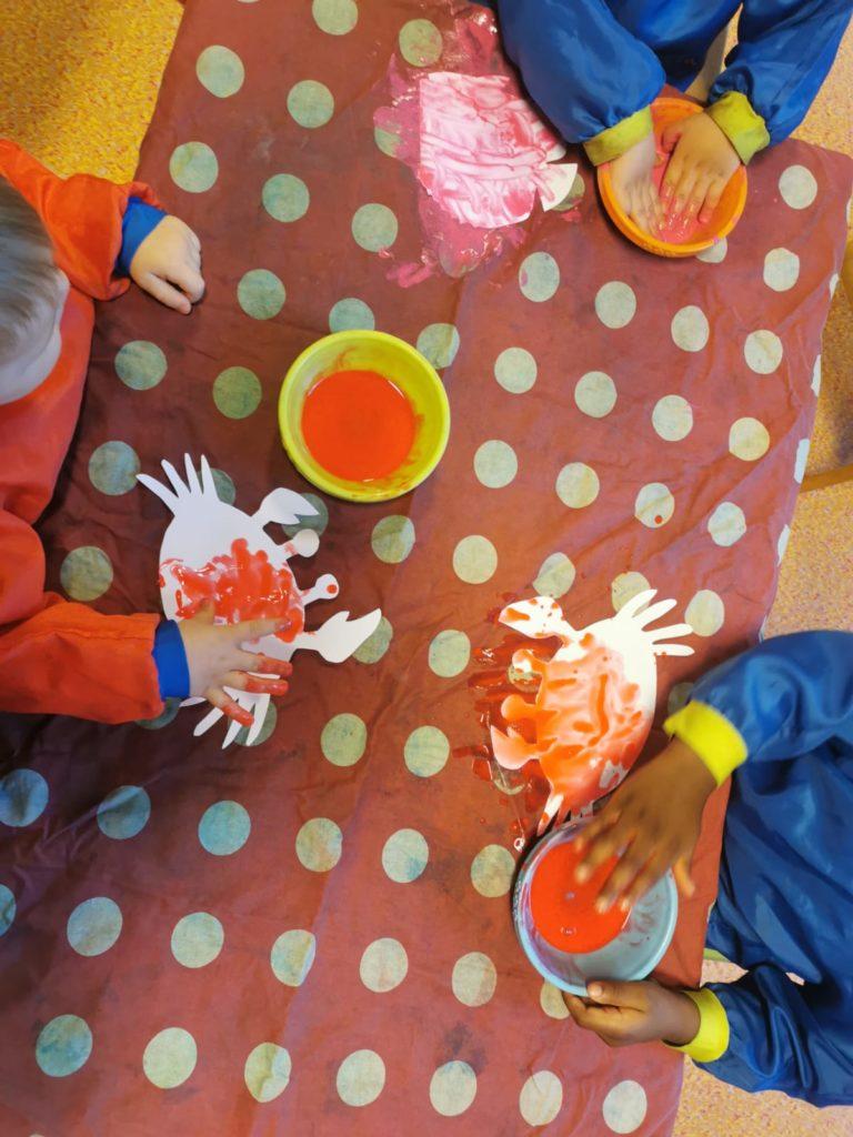 Des mains d'enfants les trempant dans la peinture orange