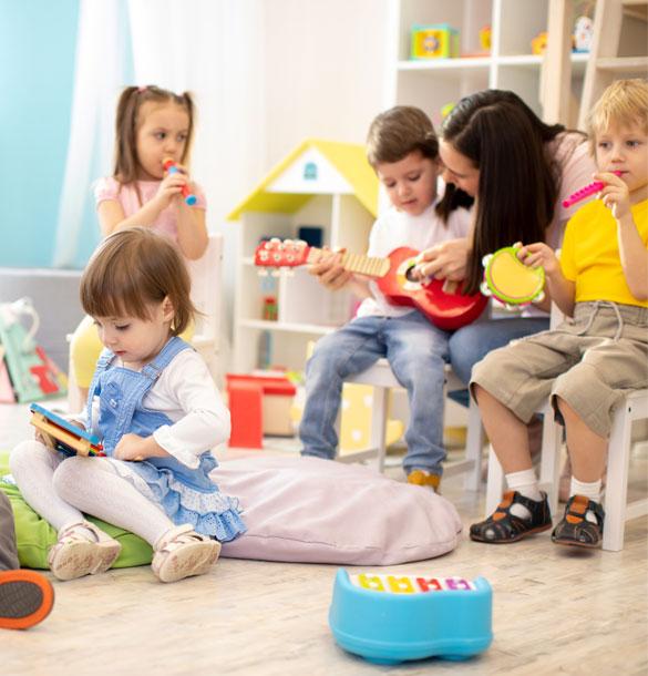 Une adulte montre comment jouer à la guitare à un enfant d'autres enfants joue aussi d'un instrument de musique