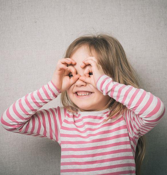 Une petite fille fait des lunettes avec ses deux mains tout en souriant